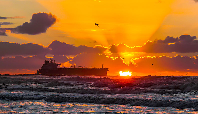 Image of a large cargo ship at sea, at sunset