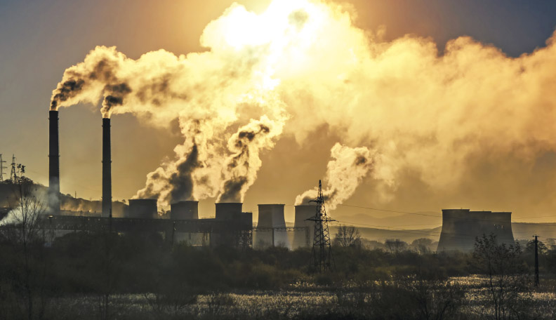 Image of factory chimneys releasing smoke into the atmosphere