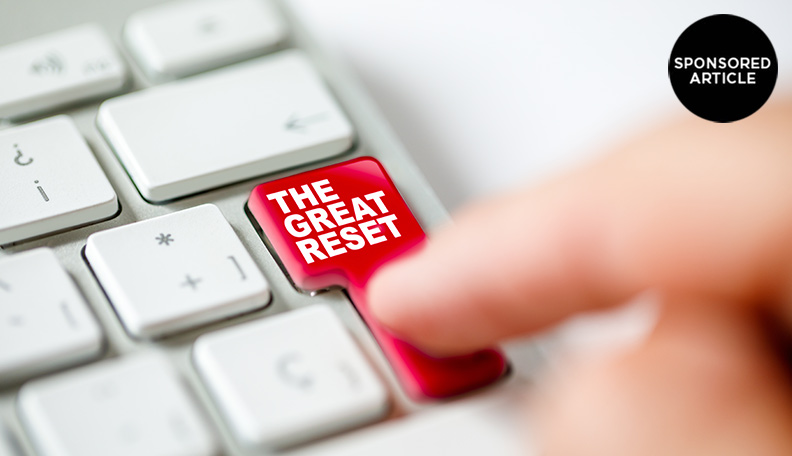 Image of a finger pressing the 'enter' key on a keyboard, which has been replaced with a red 'THE GREAT RESET' button